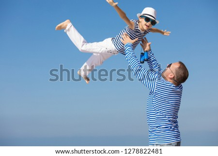 Father and son playing on the beach at the day time. They are dressed in sailor's vests. Concept of sailors on vacation and friendly family. #1278822481