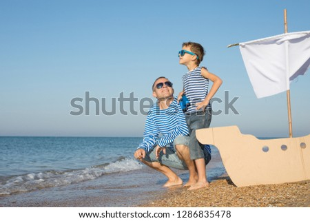 Father and son playing on the beach at the day time. They are dressed in sailor's vests. Concept of sailors on vacation and friendly family. #1286835478