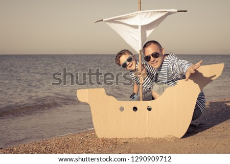 Father and son playing on the beach at the day time. They are dressed in sailor's vests. Concept of sailors on vacation and friendly family. #1290909712