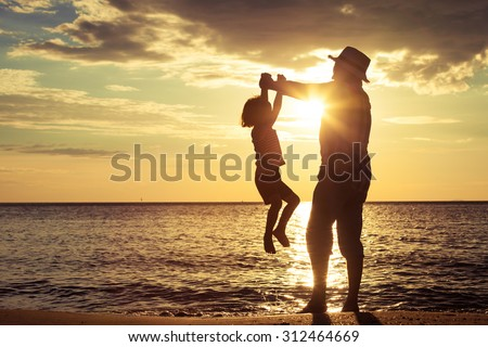 Father and son playing on the beach at the sunset time. Concept of friendly family. #312464669