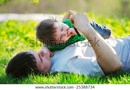 father and son playing on the grass