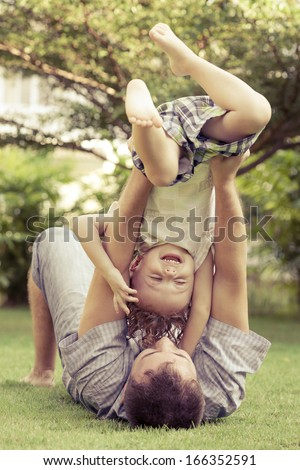 father and son playing on the meadow