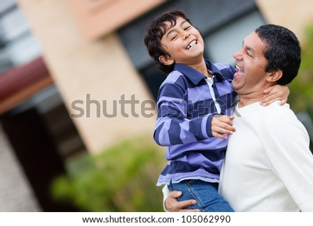 Father and son playing outdoors and looking very happy