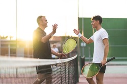 Father and Son Playing Tennis One to One. Family Doing Sport Together . Father Giving a Hug to His Son After Playing Tennis. Family Concept.