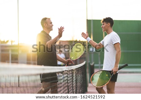 Father and Son Playing Tennis One to One. Family Doing Sport Together . Father Giving a Hug to His Son After Playing Tennis. Family Concept. Сток-фото ©