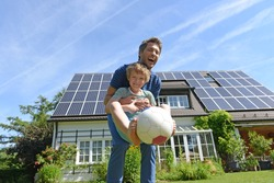 Father and son playing with ball in garden of solar paneled house
