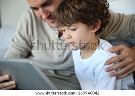Father and son playing with digital tablet
