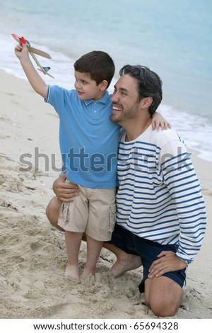 Father and son playing with toy airplane at the beach