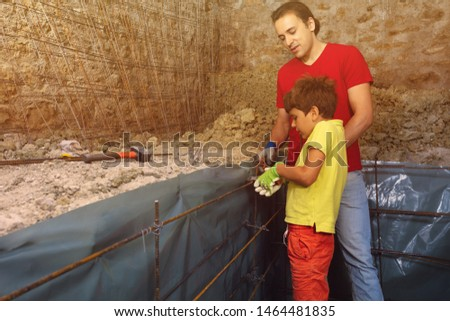 Father and son preparing framework for concrete