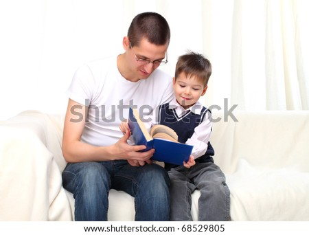 Father and son reading a book on sofa - stock photo