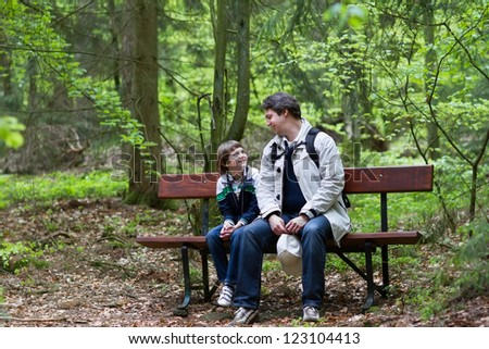 Father and son relaxing on a bench after a hike in the woods