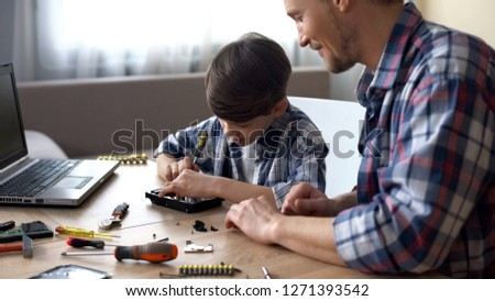 Father and son repairing small household appliances, support and reliance