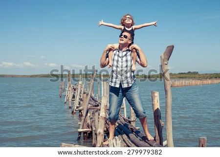 Father and son resting on the bridge in the sea at the day time. Concept of friendly family.