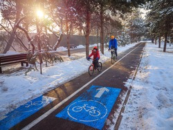 Father and son ride their bicycles along the city bike path on a sunny winter day. Cycling as a sustainable and healthy form of urban transport