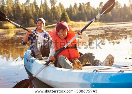 Father And Son Rowing Kayak On Lake - stock photo
