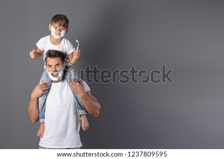 Father and son shaving on color background. Space for text #1237809595