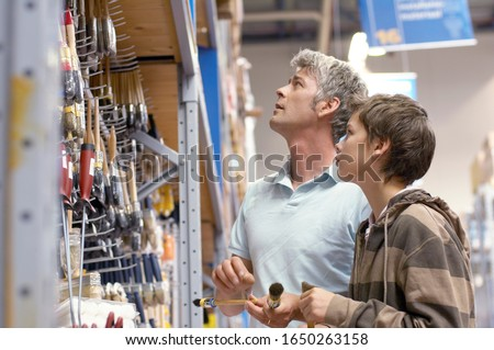 Father and son shopping for painting supplies