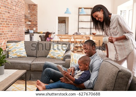 Father And Son Sit On Sofa In Lounge Using Digital Tablet