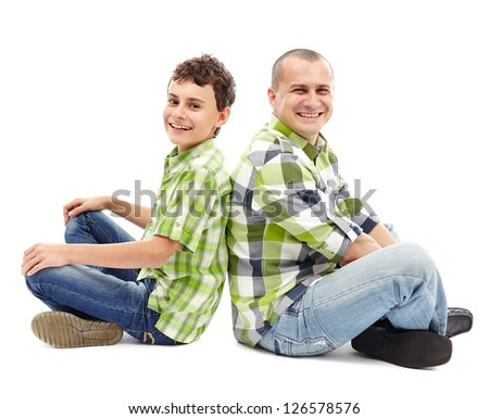 Father and son sitting back to back with crossed legs