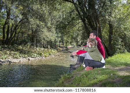 Father and son sitting by the river and learning how to fish