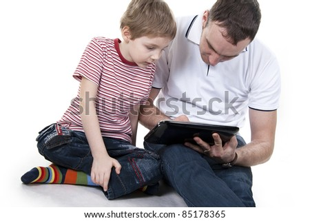 Father and son sitting on a floor with the computer on white isolation
