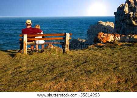 father and son sitting on bench staring out over the ocean