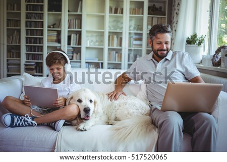 Father and son sitting on sofa and using digital tablet and laptop in living room at home