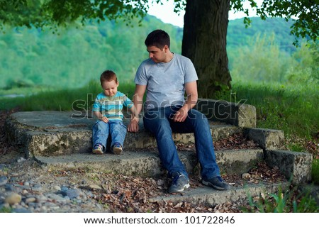 father and son sitting on stairs under an old tree. family ties concept - stock photo