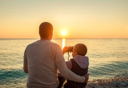 Father and son sitting on the beach and look in binocular under sunset sky with sun.