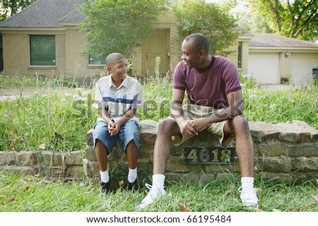 Father and son sitting on wall