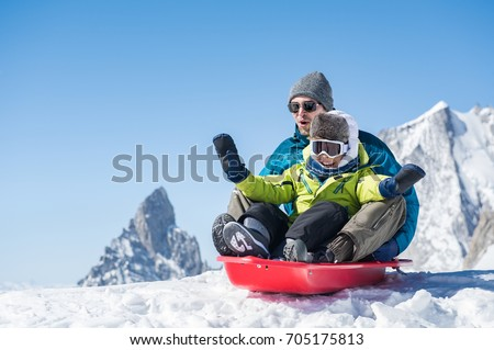 Father and son sledding during winter holiday. Happy dad and little boy playing with snow sled. Man with smiling child sitting on bobsledge in the snow with copy space.
