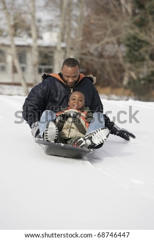 Father And Son Sledding On Snow