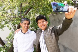 father and son smile as they take a selfie together in a garden