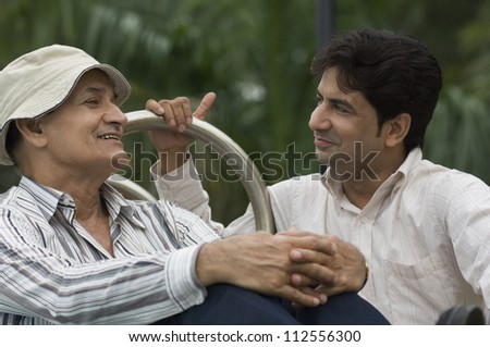 Father and son smiling in a park