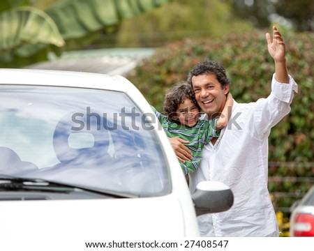 Father and son smiling with a car outdoors