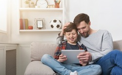Father and son spending time together and playing on digital tablet on sofa at home