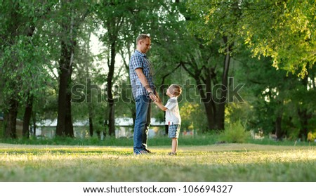 Father and son stand hand in hand in the park lawn
