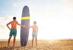 Father and son stand with surf board over sunset