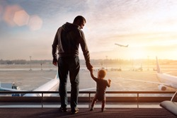 father and son standing in the airport near big window on the sunrise looking on the flying airplane wearing casual clothes