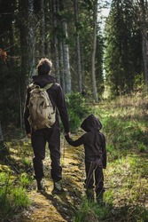 Father and son standing on forest road spending happy time together on nature background. Authentic family man kid travelling outdoors in wild woods in summer. Adventure scout relations lifestyle.