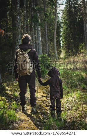 Father and son standing on forest road spending happy time together on nature background. Authentic family man kid travelling outdoors in wild woods in summer. Adventure scout relations lifestyle.  Foto stock ©
