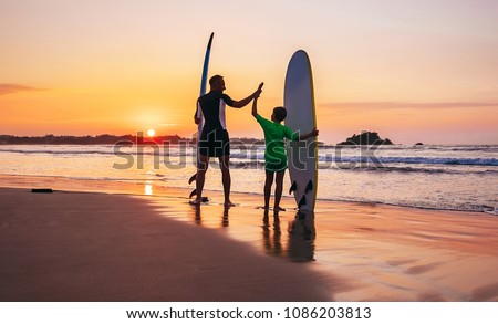 Father and son surfers stay on the sunset beach #1086203813