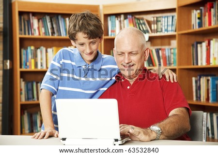 Father and son surfing the internet at the school library. - stock photo