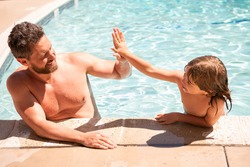 Father and son swimming in pool, summer family. Child with dad playing in swimmingpool. Family time. Summer vacation. Pool party.