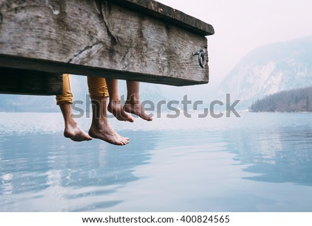 Father and son swung their legs from the wooden pier on mountain lake