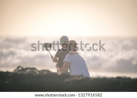 Father and son taking selfie pic at the beach. Family scene of a young male with kid making a self portrait with cellphone on stick. Souvenir from summer vacation Little boy embracing daddy at the sea