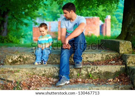 father and son talk, while sitting on old stairs outdoor