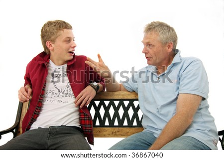 stock photo : Father and son talking with each other while sitting on a