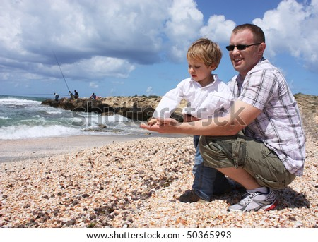 Father and son throwing shells into the sea