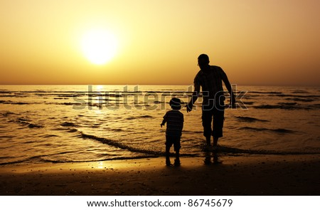 father and son to the sea at sunset